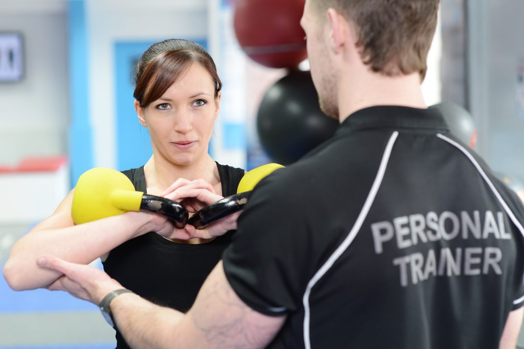 personal trainer helping woman with exercise