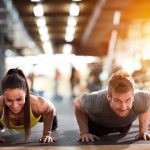 woman and man doing pushups in a gym